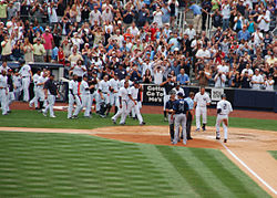 "A man in a white baseball uniform with navy pinstripes and the number ""2"" on the back of his uniform runs towards home plate, while his teammates run to meet him to celebrate."