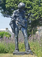 A color photograph of a bronze statue of a man holding an electric guitar.