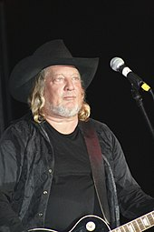 A man with long blond hair wearing a black cowboy hat and black clothing, playing a guitar