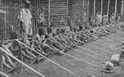 A row of more than a dozen children stretches into the distance.. They sit holding wooden looms with two pieces of thread leading from each. A man stands behind them in front of some wooden structures.