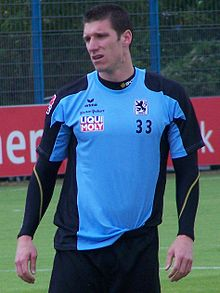 A brown-haired caucasian male in a blue and black training kit.