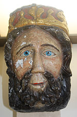 A crudely carved and brightly painted image of a king with a thick beard, bright blue eye and crown.