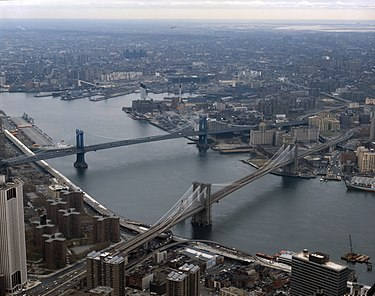 The Brooklyn Bridge in the foreground and the Manhattan Bridge beyond it, are two of the three bridges that connect Lower Manhattan with Brooklyn over the East River. LOC Brooklyn Bridge and East River 2 cropped.jpg