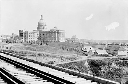 The completed Alberta Legislature Building in 1914, just above the last Fort Edmonton. The city was selected as Alberta's capital in 1905. LegislatureFortEd.jpg