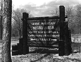 "Park sign reading: ""Lewis Mountain – Negro Area – Coffee Shop & Cottages - Campground Picnicground – Entrance"""