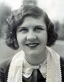 Photographie d'une jeune femme aux cheveux ondulés ramenés sur le coté et portant un foulard en dentelle