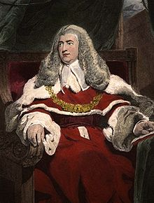 A middle age man sits in judicial robes, with a judge's wig on his head