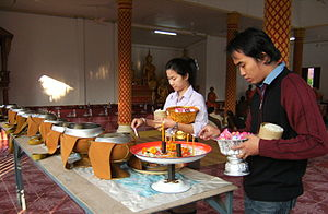 Lao people - Offering of food to monks to make merit at a temple in Vientiane