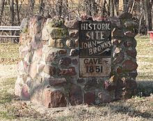 "Metal sign on stone pier, reading ""Historic Site - John Brown's Cave - 1851"""