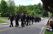 Uniformed men marching down a street