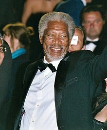 Morgan Freeman smiling and waving, facing right