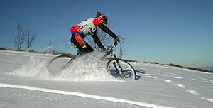 Cold-weather biking - A mountain cyclist riding through a snowy field.