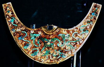 Moche Nariguera depicting the Decapitator, gold with turquoise and chrysocolla inlays. Museo Oro del Peru, Lima Nariguera Moche2.JPG