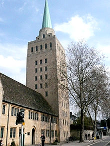 A tall light-colored stone square tower with a small metal spire; to the left, a smaller building in the same stone with a dark tiled roof