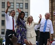 Barack and Michelle Obama and a woman and a man on an outdoor stage. The first three smile and wave. The men wear suit pants, white shirts with the sleeves rolled up, and ties. Michelle is in a colorful print dress and the other woman is in a creme business suit.