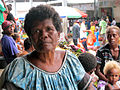 Old woman sits at the Central Market in Honiara. (10711436206).jpg