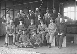 Group portrait of nineteen men, including six in military uniforms with peaked caps, in front of a biplane in a hangar