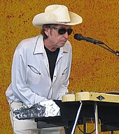 A man behind a keyboard and microphone stand, wearing a cowboy hat, sunglasses, a white dress shirt, and white pants.