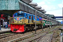 Green passenger train pulled by a blue diesel engine