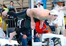 Michael Phelps si tuffa dai blocchi.