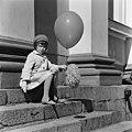 Pikkutyttö istuu vapunpäivänä ilmapallo ja vappuviuhka kädessään Tuomiokirkon portailla. - N211347 - hkm.HKMS000005-000004ks.jpg