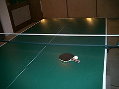 A standard table tennis table, together with a racket and ball.