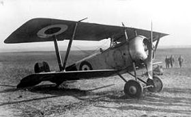 Front three-quarter view of military biplane on airfield