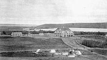 Buitenaanzicht van de Indiase industriële school Qu'Appelle in Lebret, district Assiniboia, ca.  1885. Omliggend land en tenten zijn zichtbaar op de voorgrond.