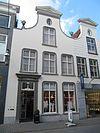 foto van Huis met gebosseerd gepleisterde, ingezwenkte halsgevel, gedekt door een driehoekig fronton