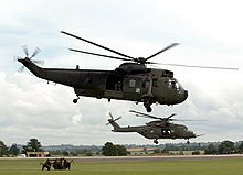 A Sea King HC4 (foreground) accompanied by a Merlin HC3 of the Commando Helicopter Force at RNAS Yeovilton.