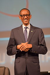 Picture of Kagame, standing, wearing a dark suit with purple tie
