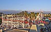 Evening photograph of the white, wooden Santa Cruz Roller Coaster, amusement park structures, and a background of eucalyptus and palm trees.