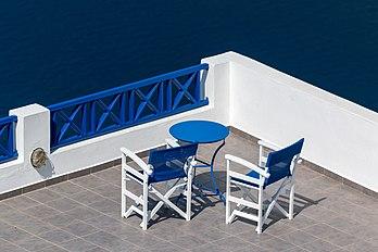 Terrasse avec table et fauteuils aux couleurs de l'architecture cycladique, à Fira, sur l'île de Santorin. (définition réelle 5410×3607)