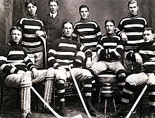 Eight young men, part of an early ice hockey team pose for a photograph, with a small silver championship trophy.