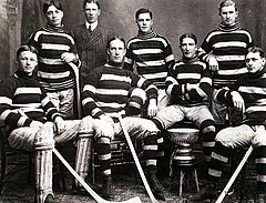 Seven men in hockey uniforms, four sitting in the front row, around the Stanley Cup trophy. Three stand in the back, with a man in a suit standing behind them.