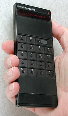 A black rectangular calculator being held in a person's right hand.