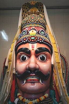 Aravan worshipped at Sri Mariamman Temple, Singapore. A cobra hood is sheltering Aravan's head.