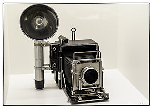 "Press camera - 4x5"" Graflex Speed Graphic press camera with optional rangefinder on left, with attached bulb flash."