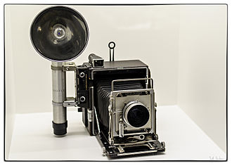 """Press camera - 4x5"""" Graflex Speed Graphic press camera with optional rangefinder on left, with attached bulb flash."""