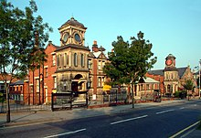 Two red-bricked buildings standing beside each other, with railings and a clock tower in front of them. The left-hand building (the school) has a sand-coloured stone tower attached to it, forming an entrance into the building. The buildings are seen from across the street, with a road and trees in front of the railings.