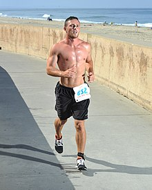 A young man competing in the 2014 Carlsbad Triathlon jogs on a paved path along a beach in Southern California. His expression shows the labor of his effort.