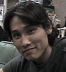 A smiling Japanese man with black hair.