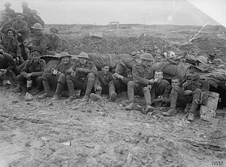 2nd Canadian Division - Canadian troops, possibly of the 25th Battalion (Nova Scotia Rifles), eating rations whilst seated on muddy ground outside a shelter near Pozieres, France, during the final stages of the Battle of the Somme, October 1916.