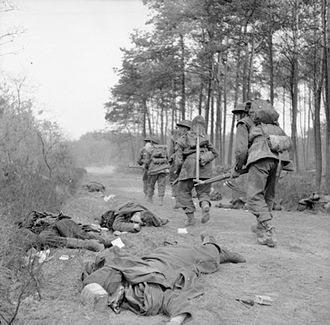 44th Infantry Brigade (United Kingdom) - Men of the 6th Battalion, King's Own Scottish Borderers advance warily along a lane, past the bodies of German soldiers, east of the Rhine, 25 March 1945.