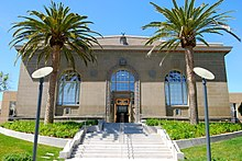 Exterior of the Richmond Branch Library. Entrance stairway is flanked by two large palm trees.