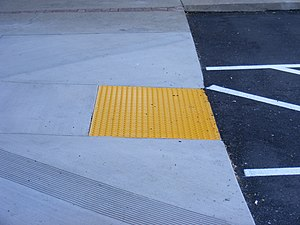 Tactile paving - A set of yellow truncated domes can be seen on the down-ramp in a parking lot.