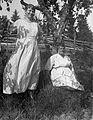 Två kvinnor i ljusa sommarklänningar under ett äppelträd. En katt klättrar i trädet - Nordiska Museet - NMA.0057557.jpg