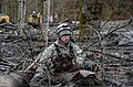 U.S. Air Force Staff Sgt. Jonathon Hernas, with the 141st Civil Engineering Squadron, Washington Air National Guard, carefully maneuvers across debris and mud while searching for missing persons in Oso, Wash 140328-Z-RI264-002.jpg