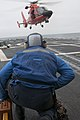 U.S. Navy Boatswain's Mate 3rd Class Travis Burke, assigned to the guided missile frigate USS Ford (FFG 54), waits for a Coast Guard MH-65 Dolphin helicopter to land on the ship's flight deck May 8 130508-N-QY316-306.jpg