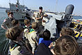 U.S. Navy Lt. Mat Rechkemmer, top, the executive officer of coastal patrol ship USS Whirlwind (PC 11), shows an MK38 Mod 2 25 mm machine gun system to Boy Scouts during a tour of the ship at Mina Salman Pier 120107-N-OX597-091.jpg